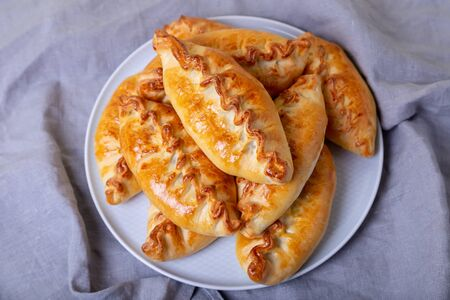 Pies (pirozhki) with cabbage. Homemade baking. Traditional Russian and Ukrainian cuisine. In the background is a dish with pies. Close-up.