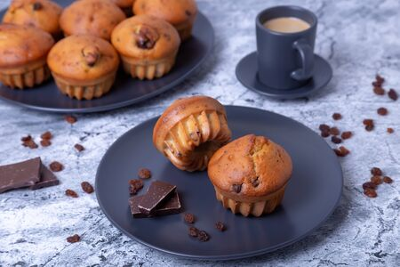 Muffins with chocolate and raisins. Homemade baking. In the background is a plate with muffins and a cup of coffee. Close-up.