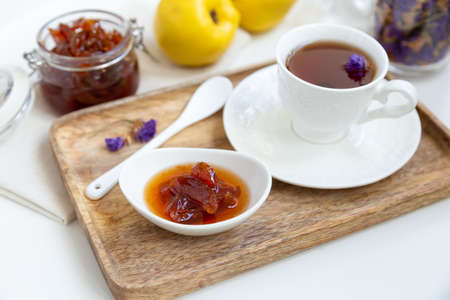 Homemade quince jam in a porcelain bowl with a cup of tea on a wooden tray. In the background is a glass jar with jam and quince. Stock Photo