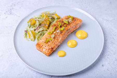 Fried salmon with fennel and orange salad with hollandaise sauce. Garnished with leeks. French dish. Close-up.