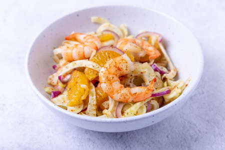 Shrimp salad with fennel, orange and red onion. Close-up, selective focus.