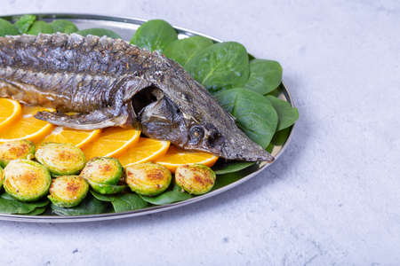 Sterlet baked (Sturgeon) with spinach, oranges and Brussels sprouts. Russian cuisine. Close-up.