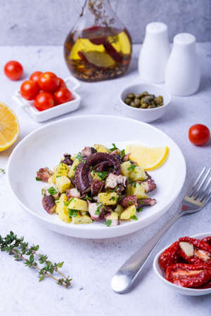 Warm salad with octopus, potatoes, tomatoes, capers and lemon on a white plate. Close-up, white background.