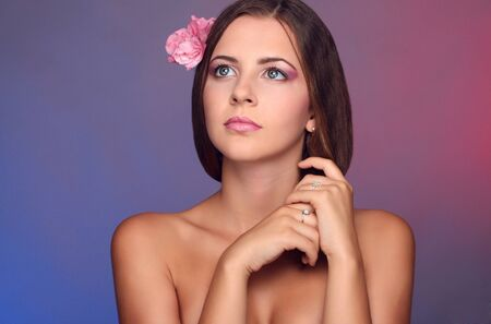 girl, pink flower in her hair, pink makeup, photostudio photo
