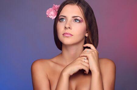 girl, pink flower in her hair, pink makeup, photostudio photo