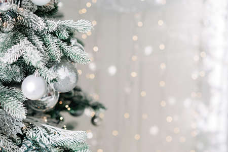 Christmas minimal background, a Christmas tree decorated with balls on a background of blurry bokeh lights. Baner, holiday card, mockup. New Year 2021. Soft selective focus, copy space.