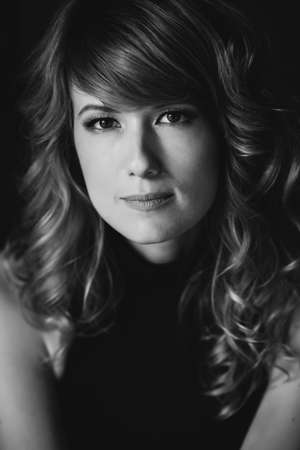Portrait of a 36 year old woman with curly hair and brown slanting eyes. Soft selective focus. Black and white art photo.