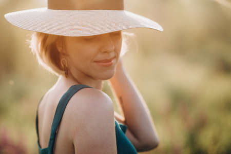 Close-up portrait of a beautiful blonde girl in a hat at dawn. Soft selective focus. Banque d'images