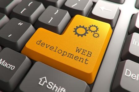 toetsenbord: Oranje Web Development knop op toetsenbord van de computer Internet Concept