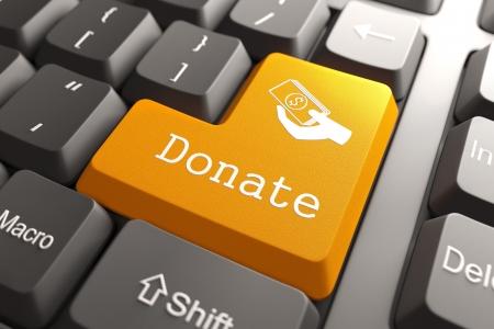 Oranje Donate knop op toetsenbord van de computer Internet Concept Stockfoto