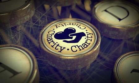 Charity Button on Old Typewriter  Grunge Background
