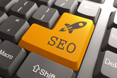 optimizing: Orange SEO Button on Computer Keyboard. Information Concept. Stock Photo