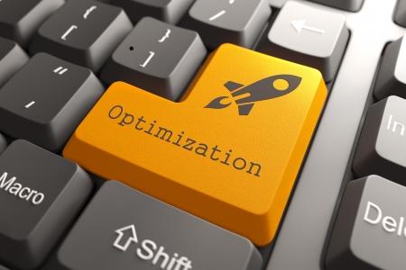 productividad: Botón anaranjado optimización en el teclado de ordenador. Concepto de negocio.