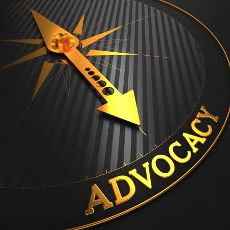 """advocate: Advocacy - Fondo del asunto. Oro aguja de la br�jula en un campo Negro apuntando a la palabra """"defensa"""". Render 3D."""
