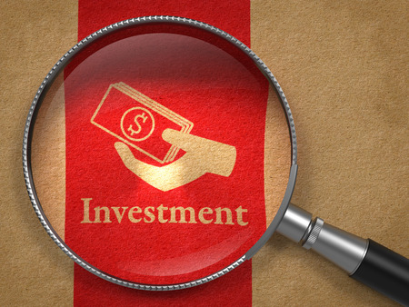 property management: Investment Concept  Magnifying Glass with Word  Investment and Icon of Money in the Hand on Old Paper with Red Vertical Line Background  Stock Photo
