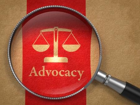 advocate: Concepto Advocacy Lupa con la defensa Palabra y el Icono de la balanza en equilibrio en el papel viejo con Red Vertical Line Background