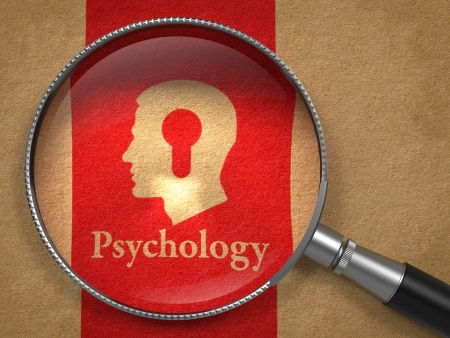 Psychology Concept  Magnifying Glass with Word Psychology and Icon of Head with a Keyhole on Old Paper with Red Vertical Line Background  photo