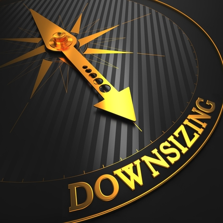 Downsizing - Business Concept  Golden Compass Needle on a Black Field Pointing to the Word  Downsizing   3D Render  photo