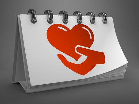 fundraiser: White Desktop Calendar with Red Icon of Heart in the Hand on Gray Background. Charity Concept. Stock Photo