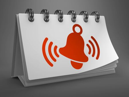 White Desktop Calendar with Red Ringing Bell Icon on Gray Background. photo