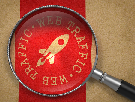 Magnifying Glass with Web Traffic Written Arround Icon of Go Up Rocket on Old Paper with Red Vertical Line Background. Internet Concept. photo