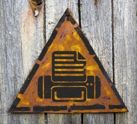 pitting: Printer Icon on Weathered Triangular Yellow Warning Sign. Grange Background.