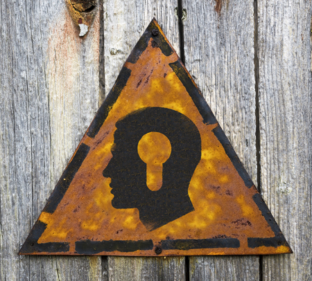 Profile of Head with a Keyhole Icon on Weathered Triangular Yellow Warning Sign. Grange Background. photo