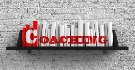 Coaching - Red Inscription on the Books on Shelf on the White Brick Wall Background. Education Concept. photo