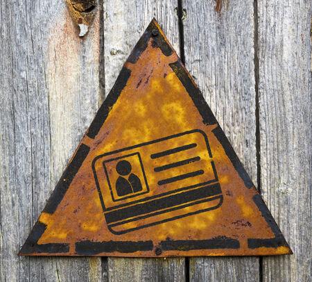 pitting: ID Card Icon on Weathered Triangular Yellow Warning Sign. Grange Background.
