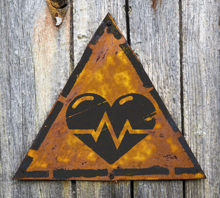 pitting: Icon of Heart with Cardiogram Line on Weathered Triangular Yellow Warning Sign. Grange Background. Stock Photo