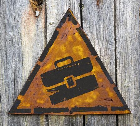 Briefcase Icon on Weathered Triangular Yellow Warning Sign. Grange Background.