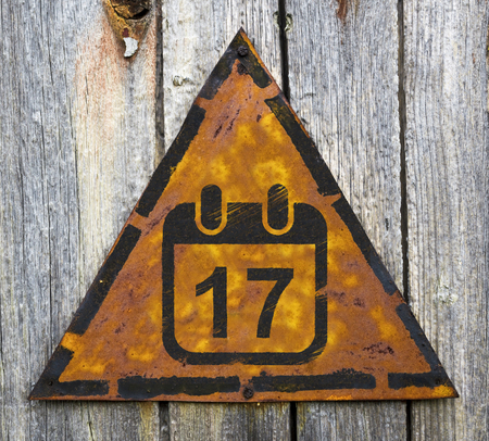 Deadline Concept. Calendar with Date Icon on Weathered Triangular Yellow Warning Sign. Grange Background. photo