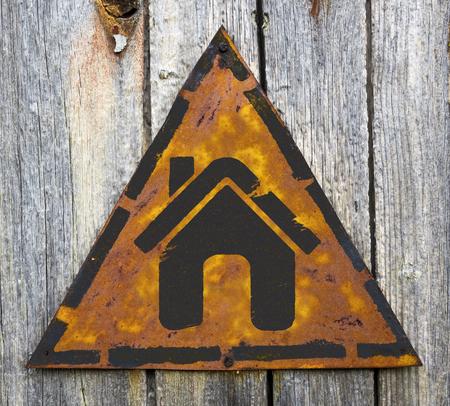 pitting: Home Icon on Weathered Triangular Yellow Warning Sign. Grange Background.