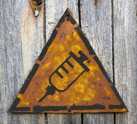 antigenic: Syringe Icon on Weathered Triangular Yellow Warning Sign. Grange Background.