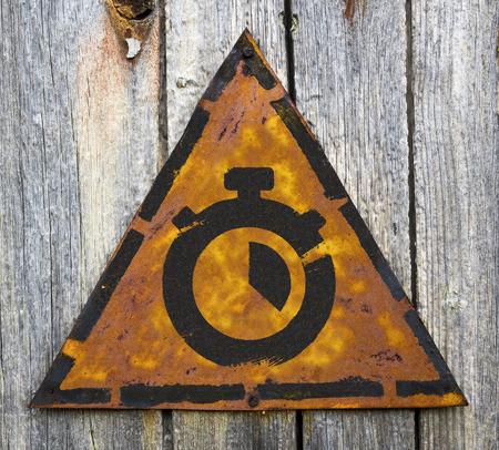 pitting: Stopwatch Icon on Weathered Triangular Yellow Warning Sign. Grange Background. Stock Photo