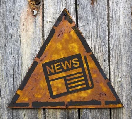 pitting: News - Newspaper Icon on Weathered Triangular Yellow Warning Sign. Mass Media Concept. Stock Photo