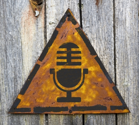 pitting: Microphone Icon on Weathered Triangular Yellow Warning Sign. Sound Concept.