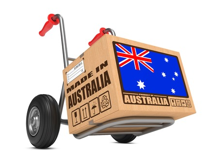 millboard: Cardboard Box with Flag of Australia and Made in Australia Slogan on Hand Truck White Background. Free Shipping Concept.