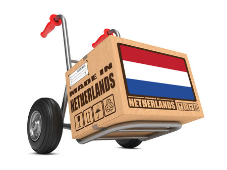 Cardboard Box with Flag of Netherlands and Made in Netherlands Slogan on Hand Truck White Background. Free Shipping Concept. photo