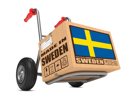 millboard: Cardboard Box with Flag of Sweden and Made in Sweden Slogan on Hand Truck White Background. Free Shipping Concept.