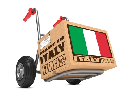 Cardboard Box with Flag of Italy and Made in Italy Slogan on Hand Truck White Background. Free Shipping Concept.