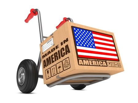 exports: Cardboard Box with Flag of USA and Made in America Slogan. Free Shipping Concept. Stock Photo