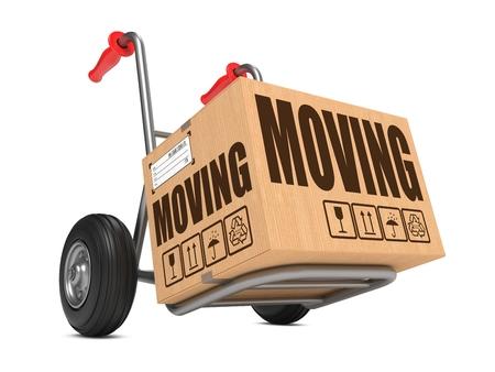 millboard: Moving - Slogan on Cardboard Box on Hand Truck White Background. Stock Photo