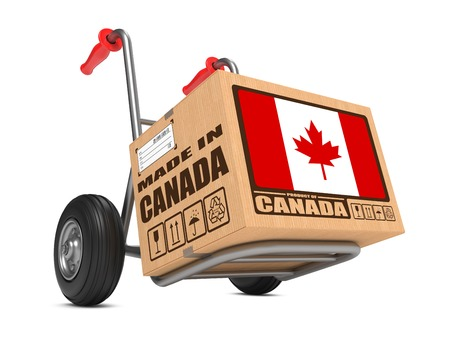 millboard: Cardboard Box with Flag of Canada and Made in Canada Slogan on Hand Truck White Background. Free Shipping Concept. Stock Photo