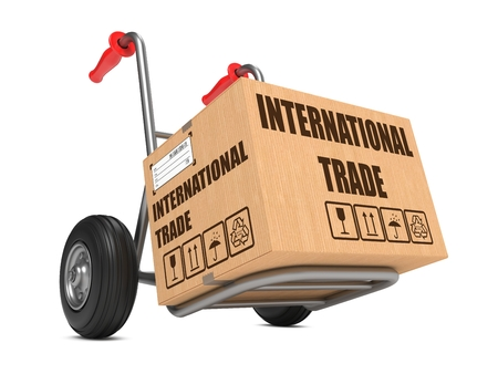 Cardboard Box with International Trade Slogan on Hand Truck White Background. Stock Photo