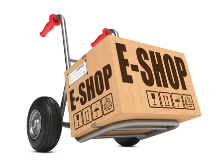 Cardboard Box with E-Shop Slogan on Hand Truck White Background.