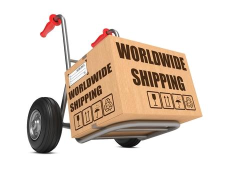 Cardboard Box with Worldwide Shipping Slogan on Hand Truck White Background. photo