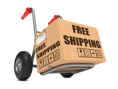 Cardboard Box with Free Shipping Slogan on Hand Truck White Background. photo