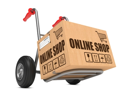 Cardboard Box with Online Shop Slogan on Hand Truck White Background.