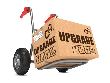 modernization: Upgrade Slogan on Cardboard Box on Hand Truck White Background.